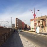 <p>En helt flad bygning langs jernbanen og nogen særprægede gadelamper</p>
