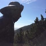 <p>Statue af pilgrim med fyrtårnet i baggrunden</p>